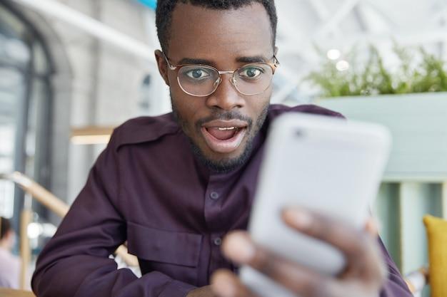 Geschokt donkere zakenman in brillen, ontvangt melding op moderne slimme telefoon, krijgt bericht om rekeningen te betalen, heeft uitdrukking verbaasd.