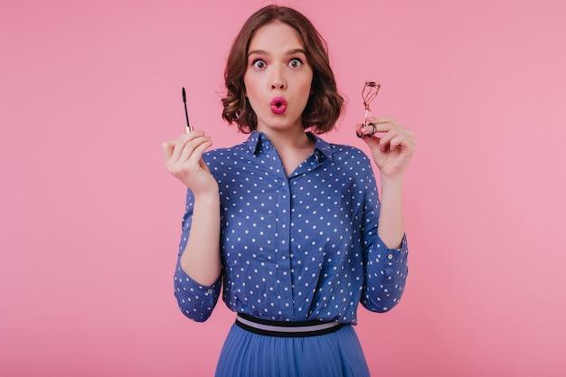Geschokt donkerogig meisje in trendy blouse poseren op roze muur met mascara. indoor foto van brunette verrast jonge vrouw doet haar wimpers.