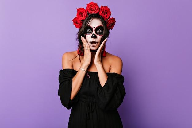 Geschokt donkerogige dame poseren met open mond in halloween. binnen schot van bange vrouwelijke zombie met rozen in haar.