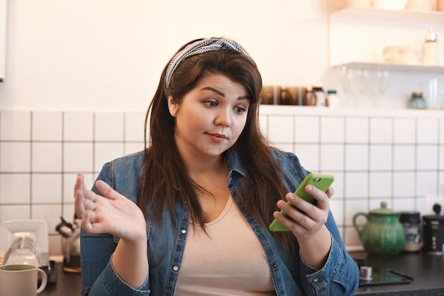 Geschokt emotionele jonge vrouw met overgewicht dragen xxl jeans jasje lezen van een sms in de keuken thuis verbaasd kijken tijdens het surfen op internet met behulp van de mobiele telefoon in de keuken tijdens het ontbijt