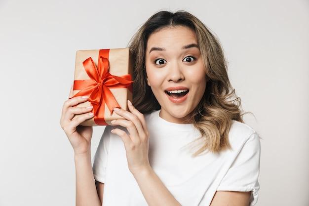 Geschokt emotionele schattige jonge vrouw poseren geïsoleerd over witte muur muur met cadeaudoosje
