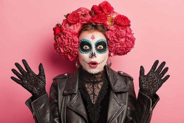 Geschokt emotionele vrouw met toegepaste make-up in vorm van schedel, geschilderde glimlach, steekt handen op, draagt zwarte kanten handschoenen, leren jas
