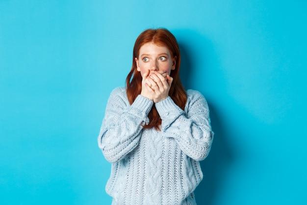 Geschokt en angstig roodharig meisje dat bang naar links staart, mond bedekt en naar adem snakt, staande over blauwe achtergrond in trui.