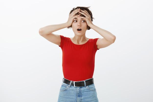 Geschokt en angstige vrouw hand in hand op het hoofd in paniek