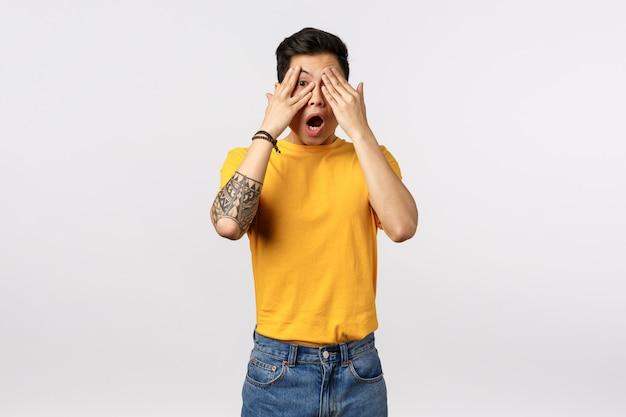 Geschokt en beschaamd jonge aziatische man ziet naakte vrouw, hijgend bedekkende ogen met handpalmen en glurend door vingers verbaasd, laat kaak van ontzag en verbazing vallen, sta op witte muur