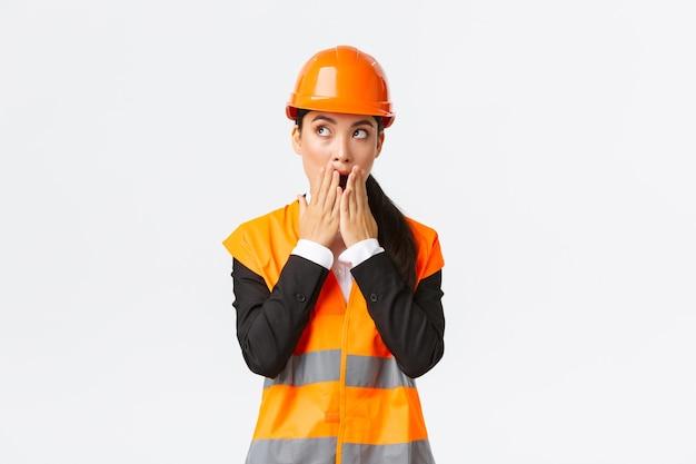 Geschokt en bezorgd aziatische vrouwelijke ingenieur, architect in veiligheidshelm en reflecterend jasje, kijkend naar de linkerbovenhoek en hijgend bezorgd, staar verbaasd, staande op een witte achtergrond