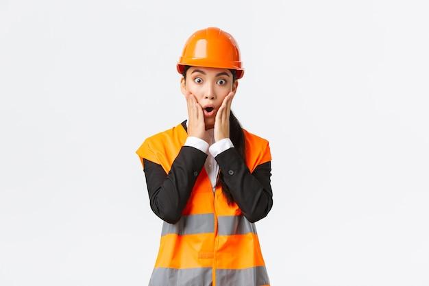 Geschokt en bezorgd aziatische vrouwelijke ingenieur die een probleem heeft met het bouwen van een gebied, staar naar het project verbaasd met een paniekgezicht, hand in hand in de buurt van de mond en hijgend, bezorgd, staande op een witte achtergrond