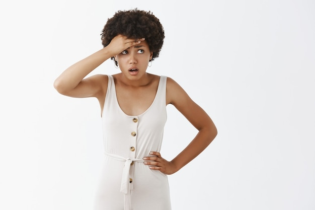 Geschokt en bezorgd stijlvol meisje poseren tegen de witte muur