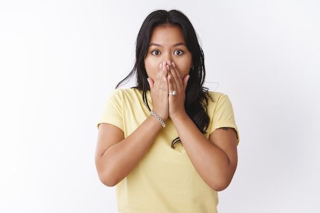 Geschokt en bezorgd verbijsterde jonge aziatische vrouw hijgend van schudde hand in hand op de mond knallende ogen bang kijkend met empathie en zorgen, staande overstuur en verontrust over de witte muur