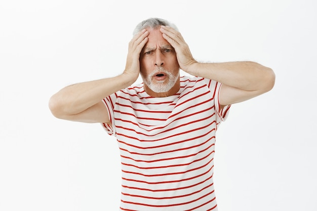 Geschokt en bezorgde senior man die in paniek raakt en bezorgd kijkt