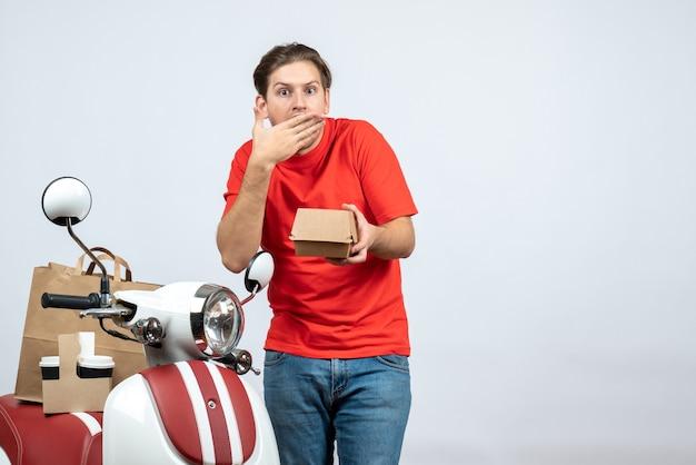 Geschokt en emotionele levering man in rode uniform staande in de buurt van scooter met kleine doos op witte achtergrond