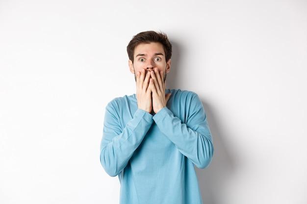 Geschokt en geschrokken blanke man, hijgend en bedekkend zijn mond met handen, starend naar iets engs, staande op een witte achtergrond