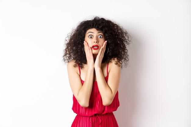 Geschokt en geschrokken vrouw staren naar iets verbazingwekkends, gezicht aanraken en camera kijken, gekleed in een rode jurk op een witte achtergrond.