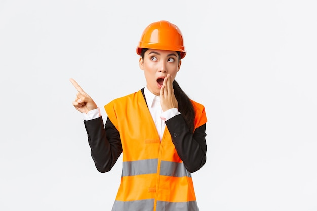 Geschokt en onder de indruk aziatische vrouwelijke ingenieur, bouwmanager in veiligheidshelm en reflecterend jack, hijgende wijzende vinger in de linkerbovenhoek verbaasd, ontdekte iets interessants