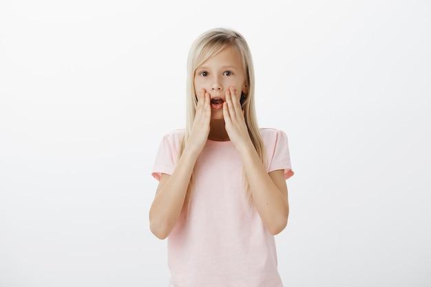 Geschokt en onder de indruk blond meisje hijgend, geamuseerd met open mond