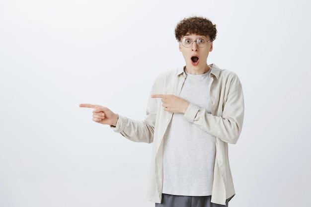 Geschokt en onder de indruk tienerjongen die tegen de witte muur poseert