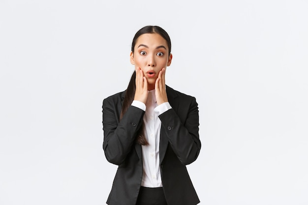 Geschokt en verbaasd aziatische vrouwelijke zakenvrouw horen groot nieuws. verkoopster ontvangt schokkend nieuws, staat in pak en kijkt verbaasd naar de camera, ondertekent een grote deal met zakenpartners