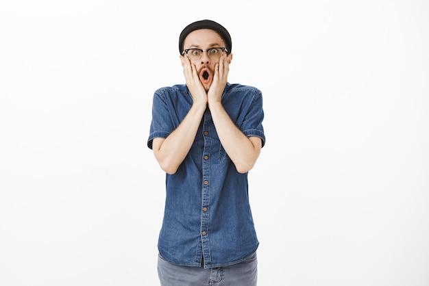 Geschokt en verbaasd bedwelmd knappe jonge kerel met snor kaak laten vallen schreeuwen wauw en staren verbaasd hand in hand op gezicht poseren