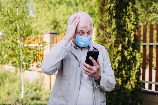 Geschokt en verbaasd man met medische gezichtsmasker met behulp van de telefoon om te zoeken naar nieuws