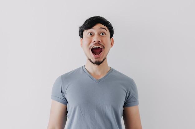 Geschokt en verrast gezicht van de mens in blauwe t-shirt geïsoleerd op een witte achtergrond