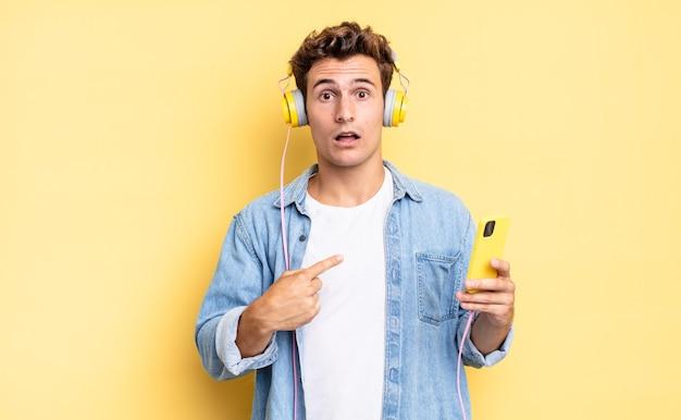 Geschokt en verrast kijken met wijd open mond, wijzend naar zichzelf. koptelefoon en smartphone concept