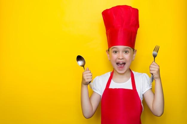 Geschokt en verrast meisje dat in het kostuum van een rode chef-kok gilt die een lepel en vork op geel houdt