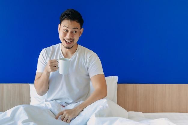 Geschokt en verraste man kijkt naar lege ruimte, word gewoon wakker op het bed