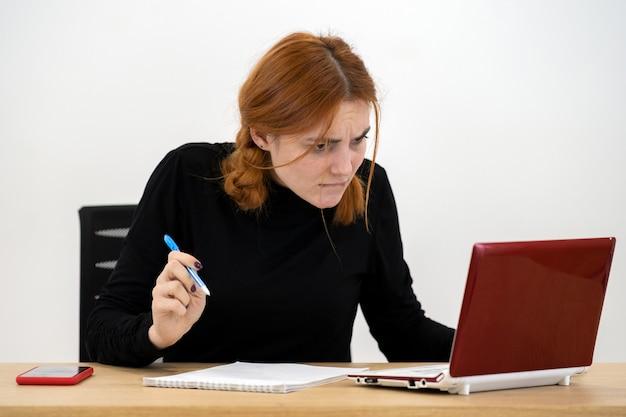 Geschokt ernstige jonge kantoor werknemer vrouw zit achter bureau met laptopcomputer, mobiele telefoon en notebook.