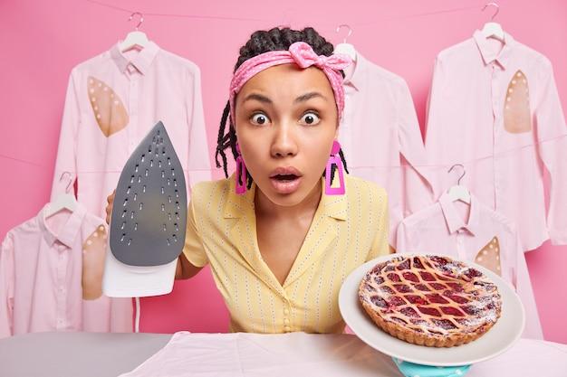Geschokt etnische vrouw staart afgeluisterde ogen naar camera draagt hoofdband en jurk heeft veel huishoudelijk werk en verantwoordelijkheden houdt elektrische ijzeren plaat van heerlijke zelfgemaakte taart met verschillende taken