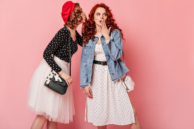 Geschokt europese dames praten op roze achtergrond. verbaasde meisjes die roddelen.