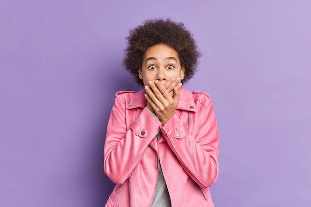 Geschokt gekrulde vrouw bedekt mond staart met schrik merkt iets vreselijks draagt stijlvolle roze jas