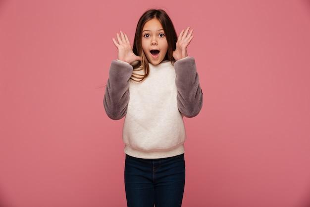 Geschokt gelukkig meisje dat in vrijetijdskleding met geopende geïsoleerde mond kijkt