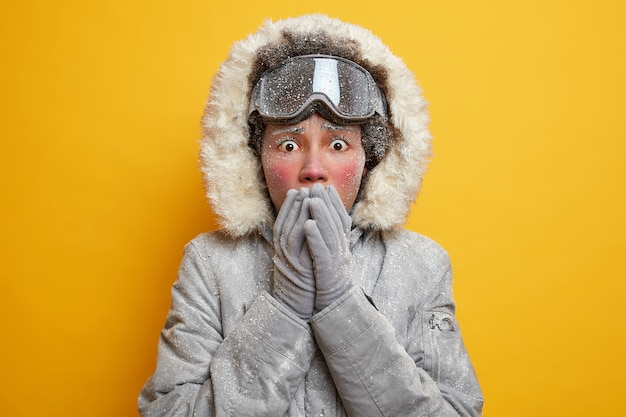 Geschokt gestresste jonge vrouw bedekt mond met handen draagt jas met capuchon en handschoenen bedekt met rijp voelt koud aan tijdens seizoensgebonden buitenactiviteiten in scandinavië.