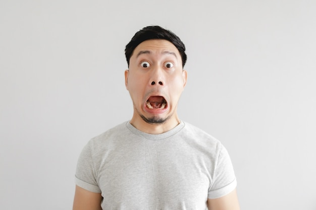 Geschokt gezicht van aziatische man in grijs t-shirt op grijs