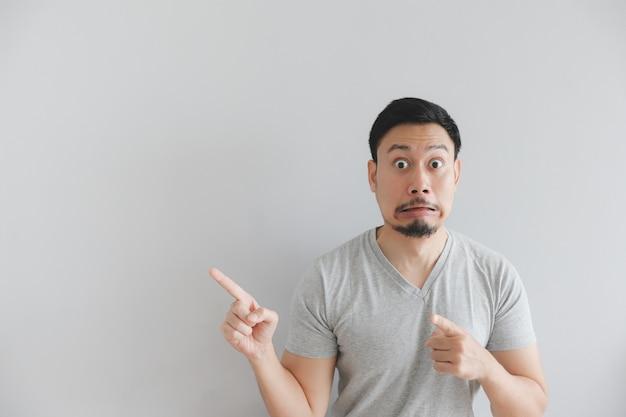 Geschokt gezicht van de mens in grijs t-shirt met hand punt op lege ruimte.