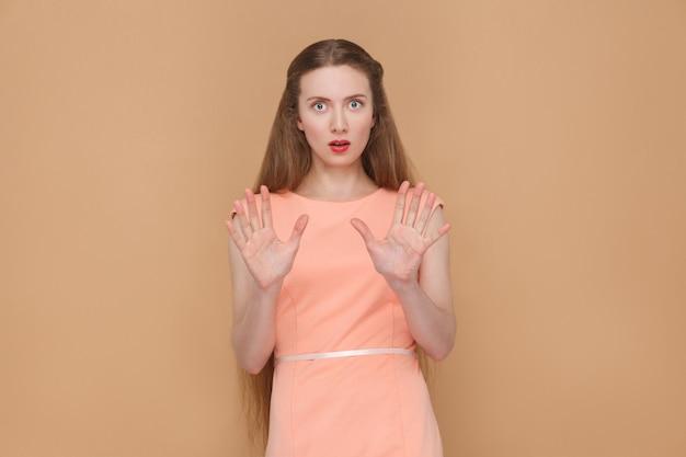 Geschokt gezicht van paniek vrouw, camera kijken. portret van emotionele schattige, mooie vrouw met make-up en lang haar in roze jurk. binnen, studio-opname, geïsoleerd op lichtbruine of beige achtergrond.