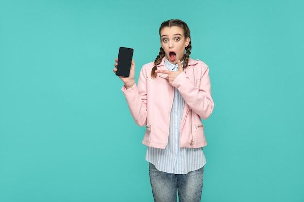 Geschokt grappig meisje in casual of hipster stijl, vlecht kapsel, staand, vasthoudend en wijzend op mobiel display, scherm met verrast gezicht, indoor studio opname, geïsoleerd op blauwe of groene achtergrond