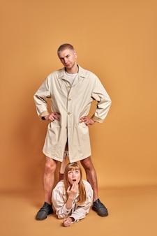 Geschokt grappige vrouw liggen onder de voeten van geïsoleerde man, portret van jonge kerel in jas poseren