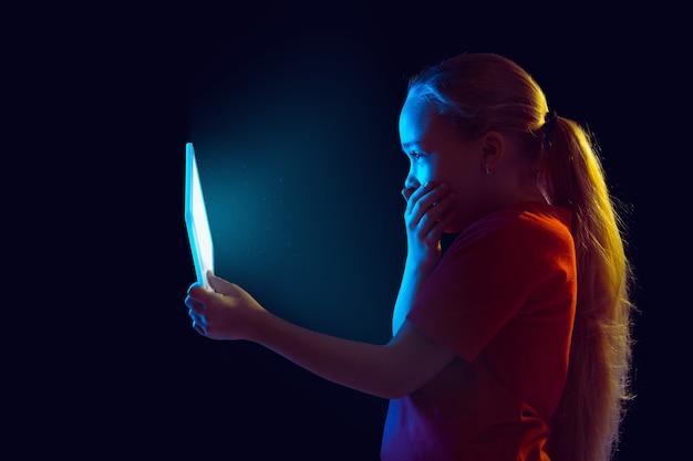 Geschokt. het portret van het kaukasische meisje dat op donkere studioachtergrond in neonlicht wordt geïsoleerd. mooi vrouwelijk model dat tablet gebruikt. concept van menselijke emoties, gezichtsuitdrukking, verkoop, advertentie, moderne technologie, gadgets.
