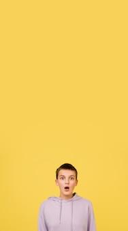 Geschokt. het portret van het kaukasische meisje dat op gele studioachtergrond met copyspace voor advertentie wordt geïsoleerd. mooi vrouwelijk model in hoodie. concept van menselijke emoties, gezichtsuitdrukking, verkoop, advertentie, mode. folder