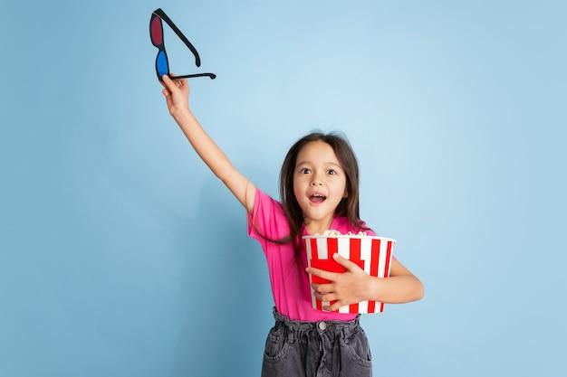 Geschokt in de bioscoop met popcorn. het portret van het kaukasische meisje op blauwe muur. mooi model in roze overhemd.
