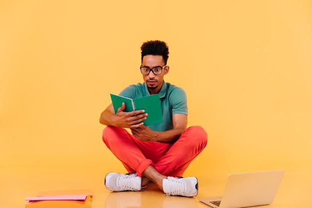 Geschokt internationale student zittend op de vloer met leerboek. binnen schot van drukke mannelijke freelancer poseren in de buurt van laptop.