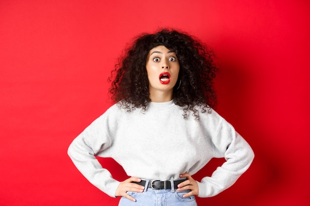 Geschokt italiaanse vrouw met krullend haar, hijgend en starend naar de camera verbaasd, open mond, staande in wit sweatshirt op rode achtergrond.