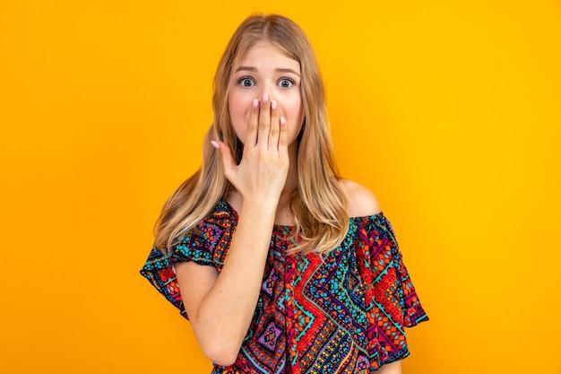 Geschokt jong blond slavisch meisje dat hand op haar mond legt en naar voren kijkt
