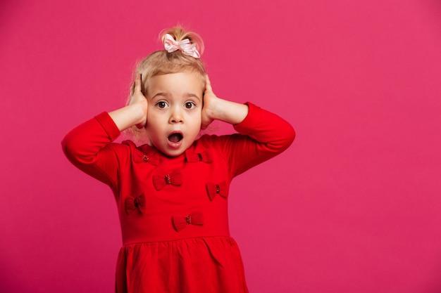 Geschokt jong blondemeisje in rode kleding die haar hoofd houdt