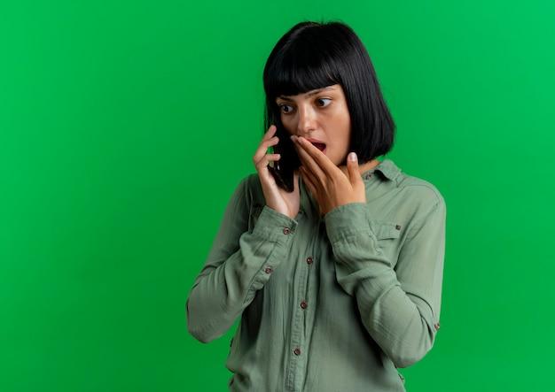 Geschokt jong brunette kaukasisch meisje legt hand op mond praten over telefoon geïsoleerd op groene achtergrond met kopie ruimte