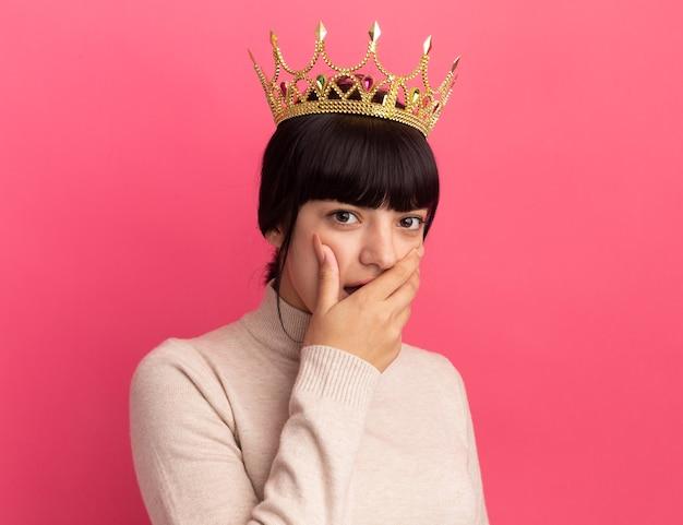 Geschokt jong brunette kaukasisch meisje met kroon legt hand op mond en kijkt naar camera op roze