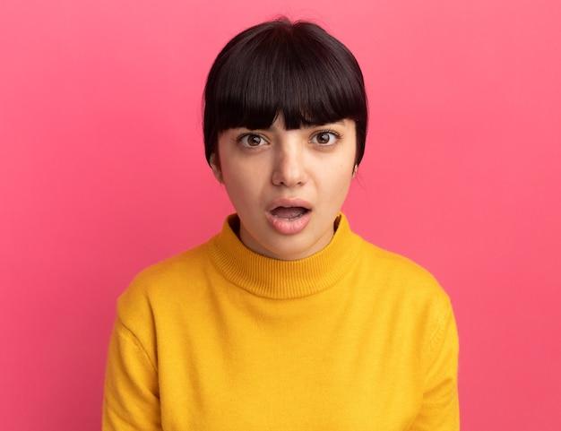 Geschokt jong donkerbruin kaukasisch meisje dat op roze muur met exemplaarruimte wordt geïsoleerd