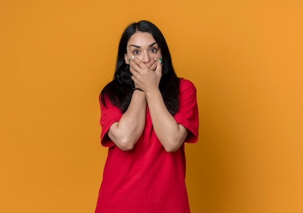 Geschokt jong donkerbruin kaukasisch meisje dat rood overhemd draagt houdt mond met twee handen die op oranje muur worden geïsoleerd