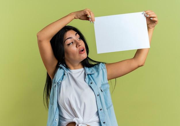 Geschokt jong kaukasisch meisje houdt en kijkt naar papier blad geïsoleerd op olijfgroene achtergrond met kopie ruimte